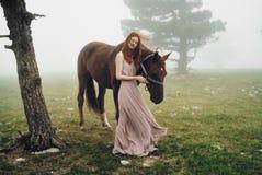 Härlig ung kvinna i bergen som går med hennes häst Royaltyfri Fotografi