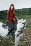 Härlig ung kvinna i bergen som går med hennes häst Royaltyfri Foto