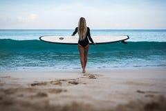Härlig ung kvinna i bikini med bränningbrädet på stranden av den tropiska ön Royaltyfria Bilder