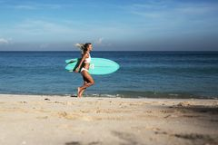 Härlig ung kvinna i bikini med bränningbrädet på stranden av den tropiska ön Arkivbild