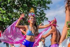 Härlig ung kvinna i bikini som går på styltor under Bloco Orquestra Voadora i service av feminism på Carnaval 2017 royaltyfri fotografi