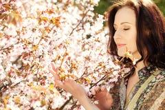 Härlig ung kvinna i blomningträdgård Arkivbild