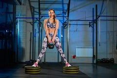 Härlig ung kvinna i den gråa sportswearen som gör övning med vikt Arg passform arkivbild