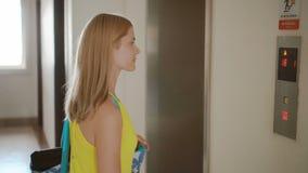 Härlig ung kvinna i den gula klänningen som väntar på en hiss Skjuta en knapp som kallar upp en elevator arkivfilmer