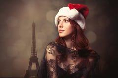 Härlig ung kvinna i den Santa Claus hatten som framme står av wo Royaltyfri Bild