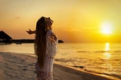 Härlig ung kvinna i den vita klänningen som omfamnar den guld- solnedgången arkivbild