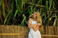 Härlig ung kvinna i den vita klänningen som står nära staketet arkivfoton