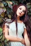 Härlig ung kvinna i det vita klänninganseendet bland färgrika sidor Royaltyfri Foto