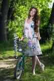 Härlig ung kvinna i en klänning och en hatt på en cykel på det Nat Royaltyfria Foton
