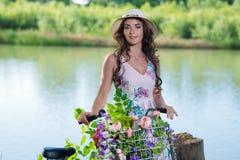 Härlig ung kvinna i en klänning och en hatt på en cykel på det Nat Royaltyfri Bild
