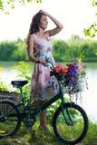 Härlig ung kvinna i en klänning och en hatt på en cykel på det Nat Royaltyfri Fotografi