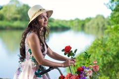 Härlig ung kvinna i en klänning och en hatt på en cykel på det Nat Royaltyfri Foto