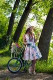 Härlig ung kvinna i en klänning och en hatt på en cykel på det Nat Arkivbild