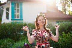 Härlig ung kvinna i en krans av blommor och ett ljust klänningsammanträde på gräsståenden i natur, glädjen av liv, leende Fotografering för Bildbyråer