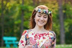 Härlig ung kvinna i en krans av blommor som ler ståenden på naturen, glädjen av liv, leende Fotografering för Bildbyråer