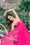 Härlig ung kvinna i en lång aftonklänning som poserar i naturen som framkallar den arkivfoton
