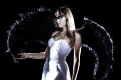 Härlig ung kvinna i en lång vit klänning och med svarta vingar Arkivbilder