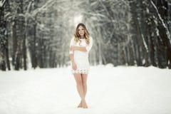 Härlig ung kvinna i en ljus klänning och barfota i snön royaltyfri fotografi