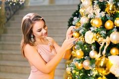 Härlig ung kvinna i en rosa elegant aftonklänning som blir i en chic korridor och upp på klär ett julträd med den gula bollen fotografering för bildbyråer