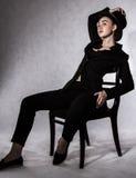 Härlig ung kvinna i en svart hatt och ett svart omslag Royaltyfria Foton