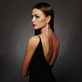 Härlig ung kvinna i en svart sexig klänning som poserar i studion, lyx skönhetbrunettflicka Royaltyfri Bild