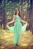 Härlig ung kvinna i en turkosklänning i en pinjeskog Arkivfoto