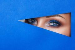 Härlig ung kvinna i ett hål i blått papper, härligt ljust smink royaltyfri foto