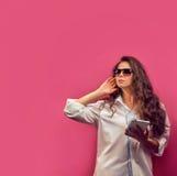 Härlig ung kvinna i exponeringsglas med hörlurar som rymmer en whit Arkivfoto