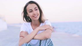 Härlig ung kvinna i ljus sommarkläder som sitter på pir på hamnen på gryning Den unga caucasian kvinnlign håller ögonen på lager videofilmer