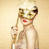 Härlig ung kvinna i mystisk guld- Venetian maskering Arkivfoton