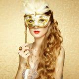 Härlig ung kvinna i mystisk guld- Venetian maskering Royaltyfri Fotografi
