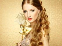 Härlig ung kvinna i mystisk guld- Venetian maskering Royaltyfria Bilder