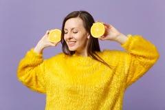 Härlig ung kvinna i pälströjan som håller ögon stängda för att rymma halfs av ny mogen orange frukt som isoleras på violett paste royaltyfri foto