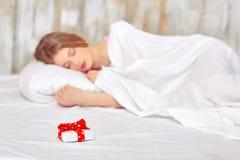 Härlig ung kvinna i säng med en gåva Arkivfoton