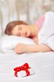 Härlig ung kvinna i säng med en gåva Arkivbilder