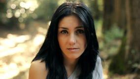 Härlig ung kvinna i skogen som ser closeupen stock video