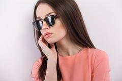 Härlig ung kvinna i solglasögon som ser kameran Royaltyfri Foto