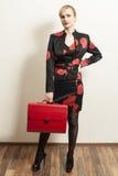 Härlig ung kvinna i svart och röd klänning med det röda fallet royaltyfri foto