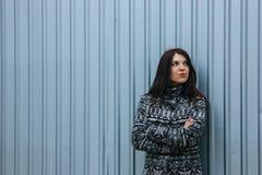 Härlig ung kvinna i tillfällig kläder mot staketet arkivfoto