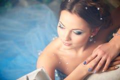 Härlig ung kvinna i ursnygg blå lång klänning som Cinderella med perfekt smink- och hårstil Arkivfoto