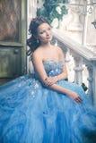 Härlig ung kvinna i ursnygg blå lång klänning som Cinderella med perfekt smink- och hårstil Royaltyfri Bild