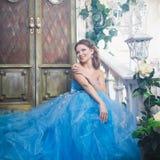 Härlig ung kvinna i ursnygg blå lång klänning som Cinderella med perfekt smink- och hårstil Royaltyfri Fotografi