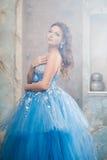Härlig ung kvinna i ursnygg blå lång klänning som Cinderella med perfekt smink- och hårstil Arkivbild
