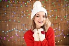 Härlig ung kvinna i varm kläder som poserar på suddig ljusbakgrund fira santa för modern för hattar för berömjuldottern slitage royaltyfri bild
