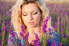 Härlig ung kvinna i violetta blommor Arkivbilder