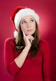 Härlig ung kvinna med att tänka för santa hatt royaltyfri bild