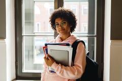 Härlig ung kvinna med böcker och digitalt minnestavlaanseende på fönstret royaltyfria foton