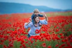 Härlig ung kvinna med barnflickan i vallmofält lycklig familj som har roligt i natur utomhus- stående i vallmo moder med royaltyfri fotografi
