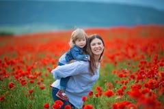 Härlig ung kvinna med barnflickan i vallmofält lycklig familj som har roligt i natur utomhus- stående i vallmo moder med royaltyfria bilder