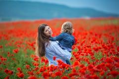 Härlig ung kvinna med barnflickan i vallmofält lycklig familj som har roligt i natur utomhus- stående i vallmo moder med arkivbilder